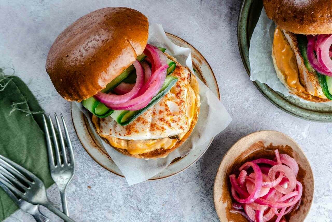 Pollack fish burger with cajun mayo, cucumber and pickled red onions