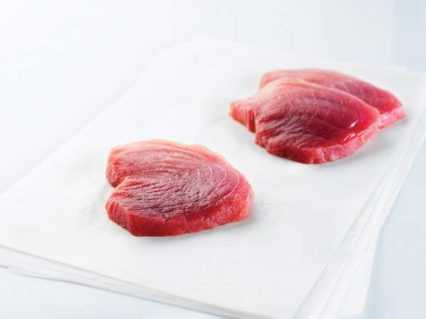 Two red tuna steaks on white paper