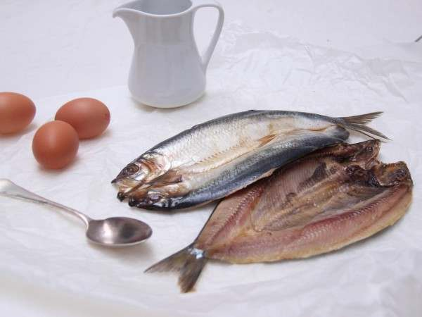 Two pairs of kippers with eggs and a jug on white paper
