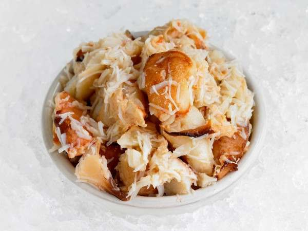 Cooked white crab meat in white dish on ice