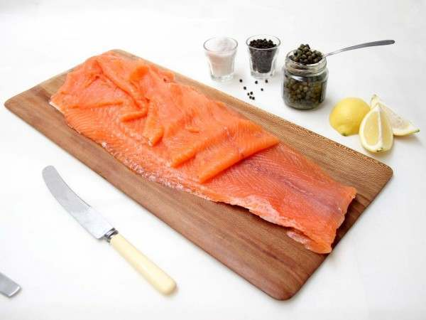 Long sliced side of smoked salmon on wooden serving board
