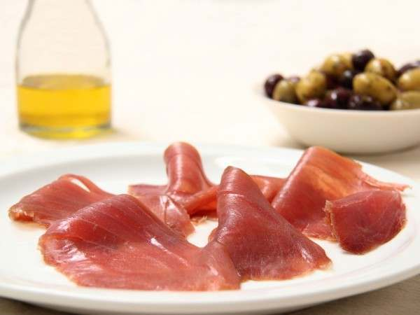 Thin slices of smoked tuna served with olives and olive oil