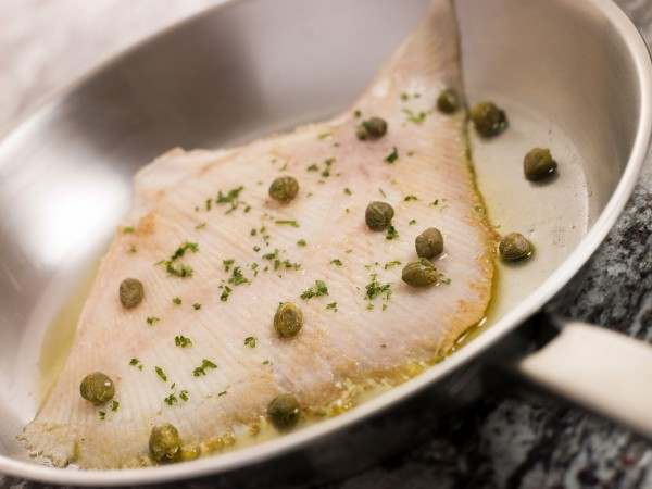 Whole trimmed skate wing in a pan with capers