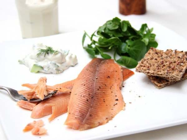 Two smoked trout fillets served with salad and crackers