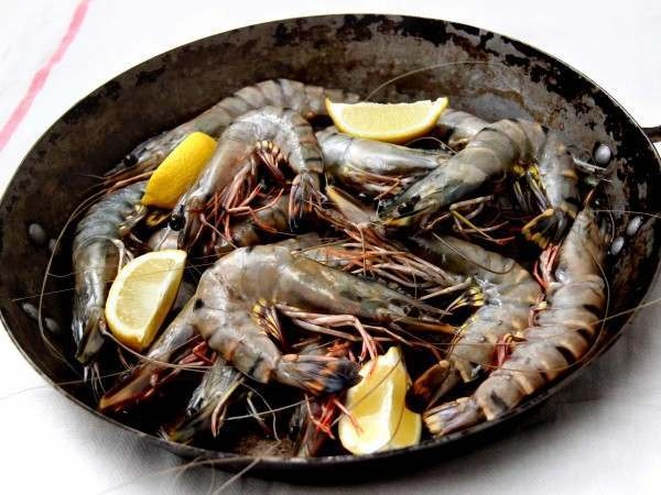 Whole king prawns in a pan with lemon