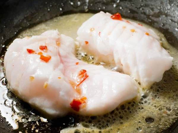 Monkfish misshapes cooking in a pan with butter and chilli