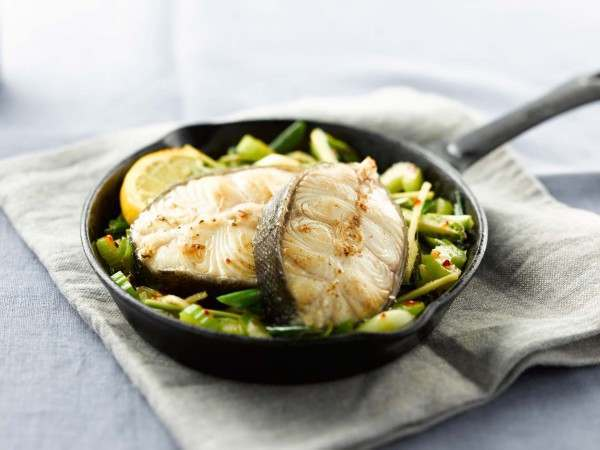 Two black cod on the bone steaks in cooked presentation in pan with green vegetables