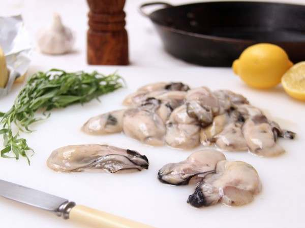 Raw oyster meat on white chopping board