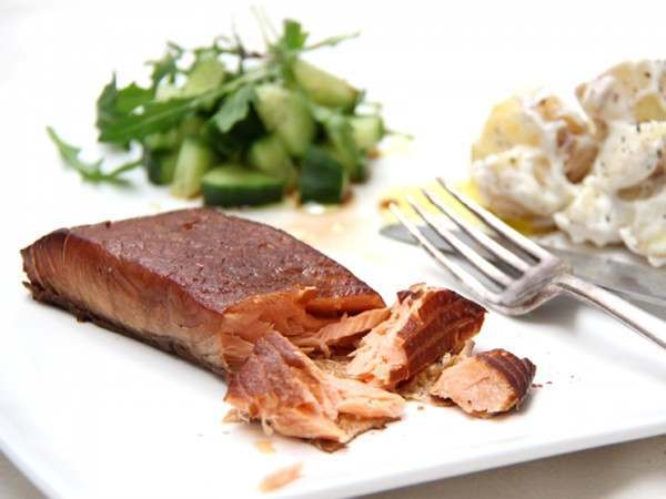 Hot smoked salmon steak served with salad and potato salad