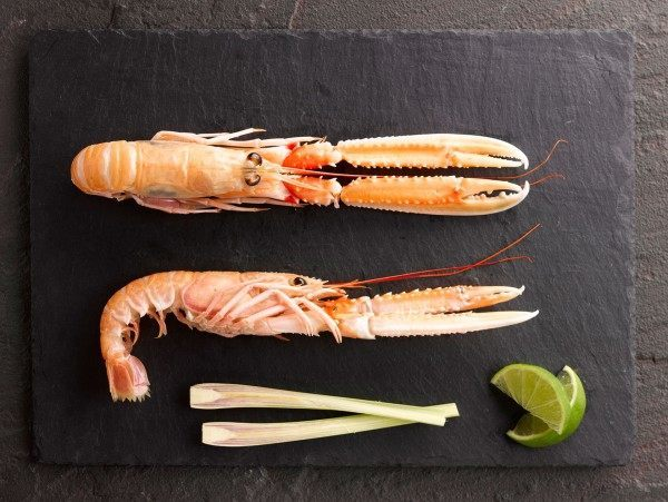 Two fine langoustines on a slate board with lemongrass and lime