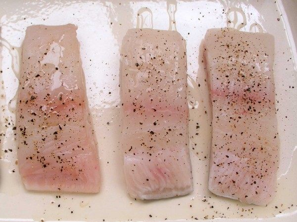 Fillet portions of wild halibut in a baking tray with seasoning