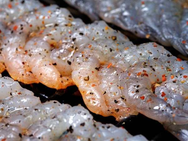Peeled king prawns on a skewer being grilled with pepper and spices