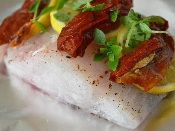 Raw stone bass fillet steaks with tomatoes and herbs