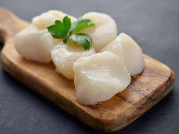 Raw king scallops on wooden chopping board