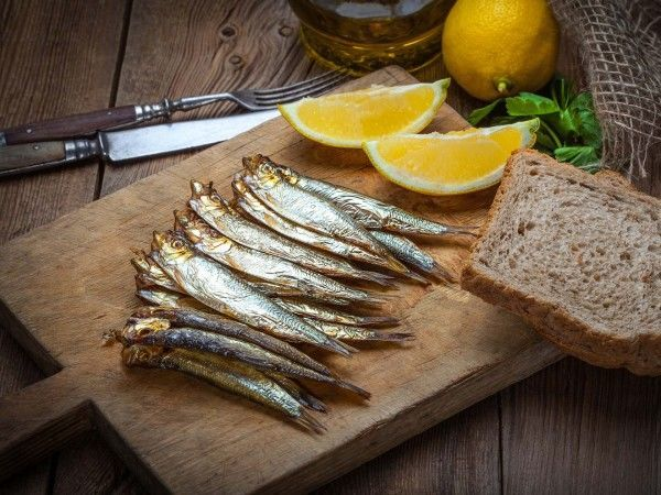 Smoked sprats on a wooden board