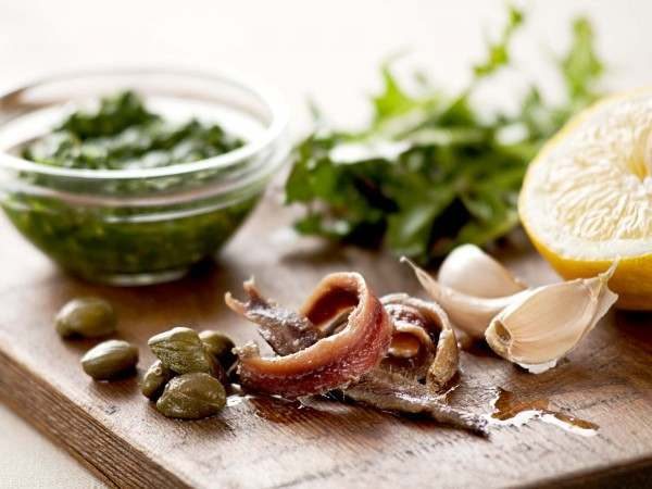 Ortiz anchovy fillets on wooden chopping board with capers and garlic