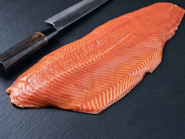 A whole king salmon fillet next to a knife