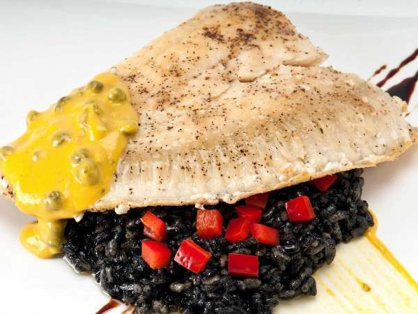 A cooked turbot fillet portion on black squid ink rissotto